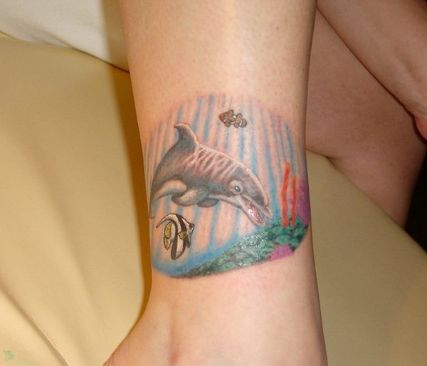 Outstanding Blue Ink Dolphin And Fish Tattoo For Women Leg