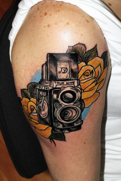 Fantastic Yellow Green And Black Color Ink Camera Tattoo On Biceps For Girls