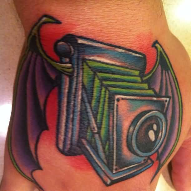 Groovy Green Blue Black And Red Color Ink Bat Winged Camera Tattoo On Hand For Boys