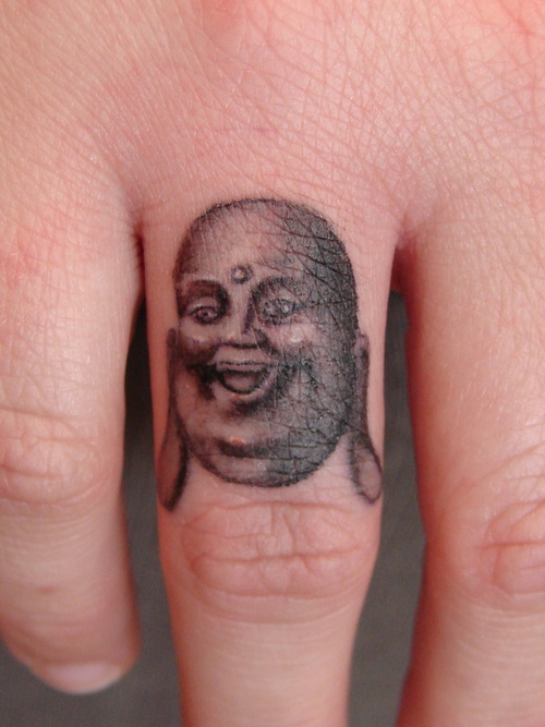 Glowing Buddha Face Tattoo On Finger For Girls